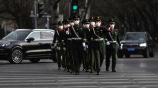 ضباط في القوات العسكرية في الصين يرتدون أقنعة للوجه لاحتواء انتشار مرض فيروس كورونا يمشون في شارع في بكين، الصين 18 مارس/ آذار 2020.