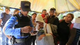 Un oficial de policía hondureño mientras revisaba la documentación a varios migrantes de la caravana en el punto de supervisión de Agua Caliente, en la frontera entre Honduras y Guatemala el 15 de enero de 2019.