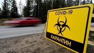"""Un panneau portant l""""inscription """"Quarantaine Covid-19"""" à l'entrée du village de Pervomaiskoye près de Saint-Petersburg, le 3 mai 2020"""