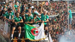 Los jugadores de Argelia muestran el trofeo de la Copa Africana de Naciones a los miles de aficionados durante el desfile de bienvenida en Alger, el 20 de julio de 2019.