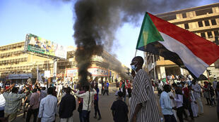 A Sudanese man waves his country's flag during protests on December 19, 2020 in the capital, Khartoum, marking the second anniversary of the start of a revolt that toppled the previous government.