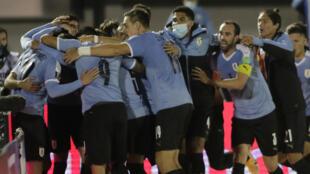 los jugadores de Uruguay celebran el gol de Maximiliano Gómez (tapado) para darle la victoria sobre Chile en el inicio de la eliminatorias sudamericanas para el Mundial de Catar 2022 el 8 de octubre de 2020 en el estadio Centenario de Montevideo