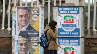 Una mujer pasa junto a carteles electorales del candidato de 5 estrellas Luigi Di Maio y el partido de Forza Italia en Pomigliano D'Arco, cerca de Nápoles, Italia, el 21 de febrero de 2018.