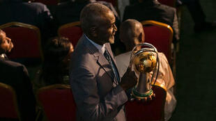 Stephen Tataw carries the trophy of the African Championship of Nations (CHAN) to the stage during the draw ceremony in Yaounde in February