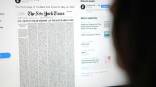 Sur un écran d'ordinateur s'affiche un tweet du New York Times montrant sa Une du lendemain, consacrée à une liste de mille personnes mortes du coronavirus, à Los Angeles le 23 mai 2020