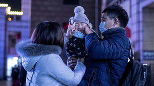 Parents put a protective mask on their baby as they stand outside Beijing railway station ahead of the Lunar New Year in Beijing on January 23, 2020