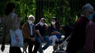 Tres personas con mascarilla descansan en un banco del parque del Retiro, en el centro de Madrid, el 10 de octubre de 2020