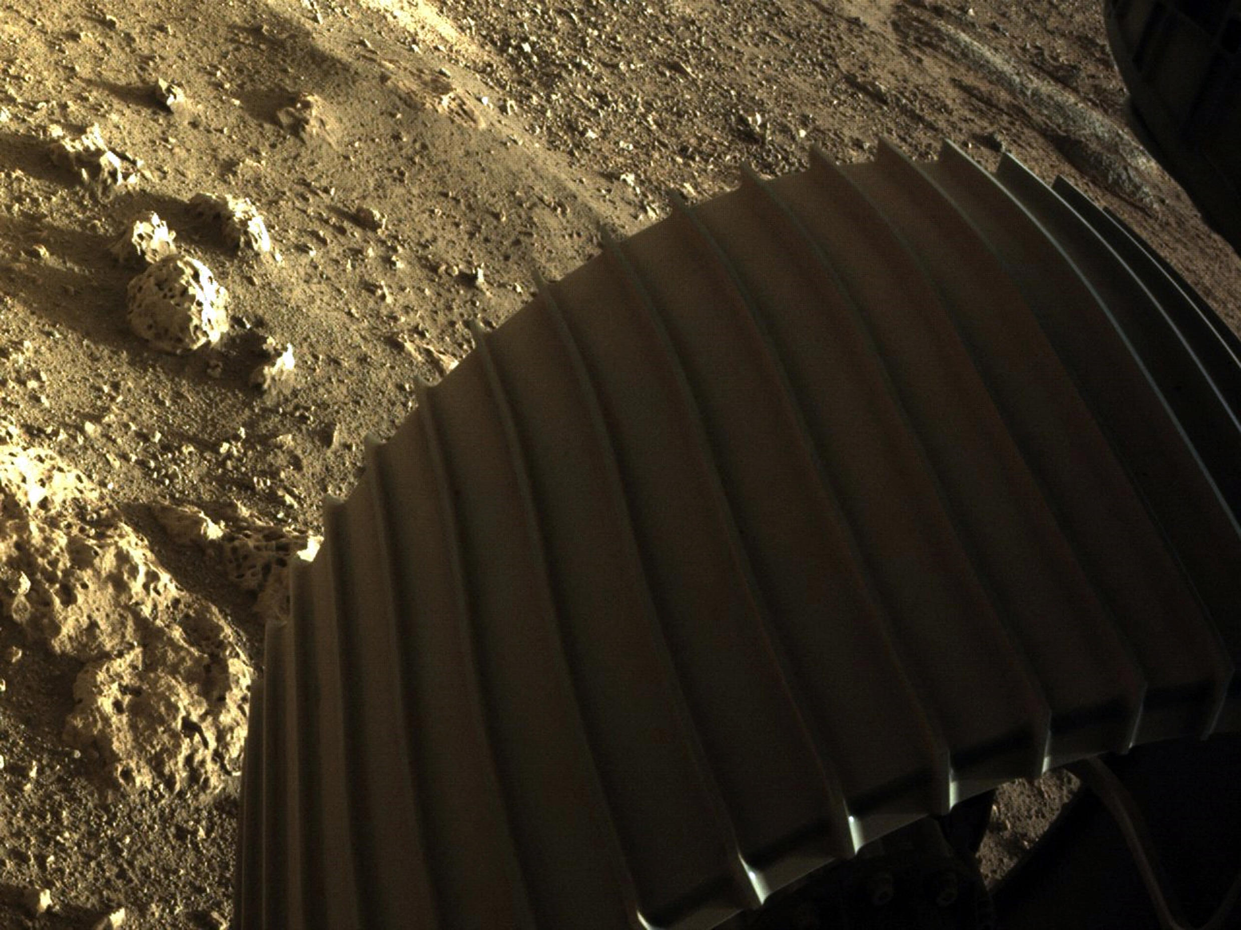 A colour image sent by Persverance shows one of the rover's six wheels with rocks thought to be more than 3.6 billion years old lying next to it.