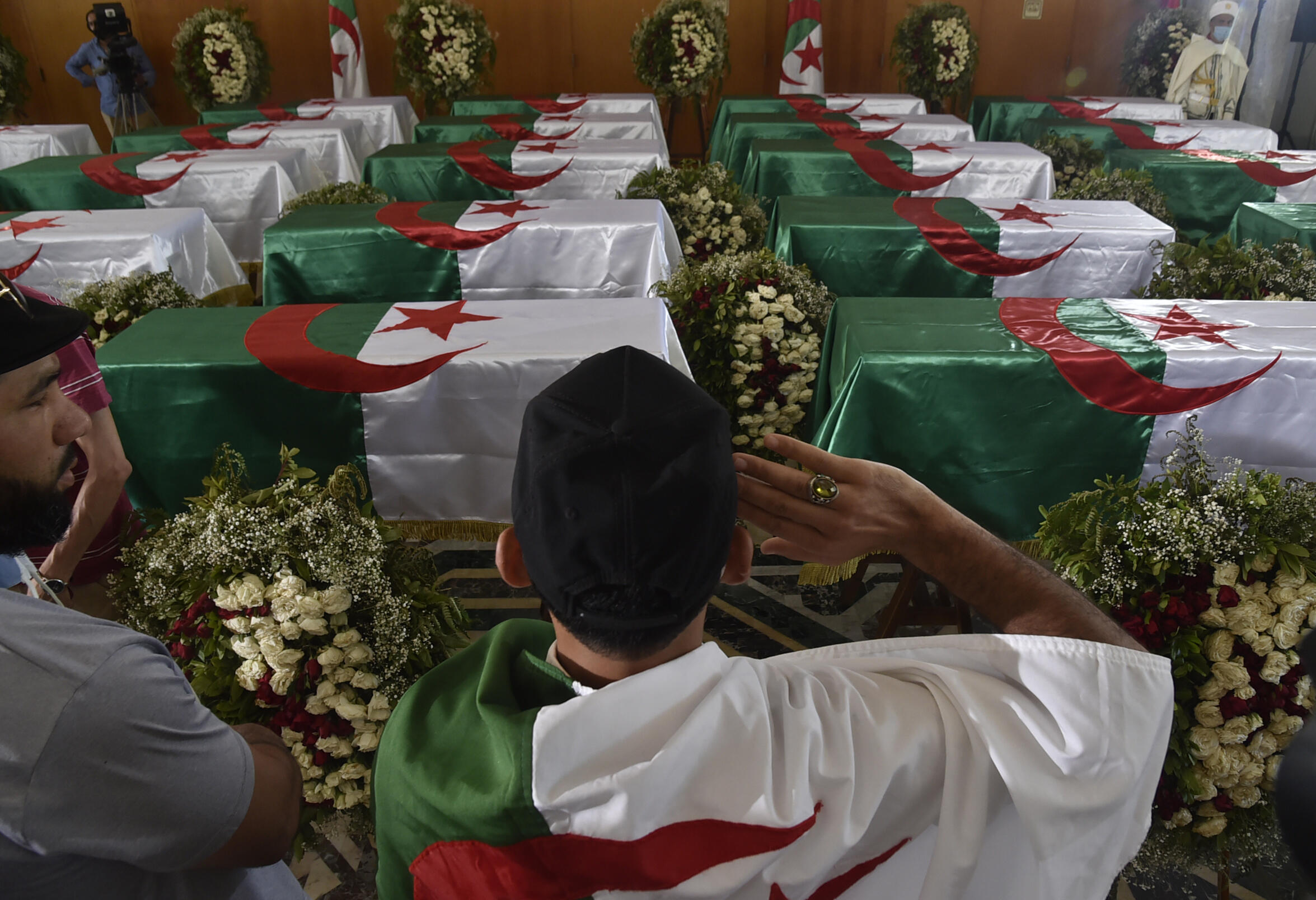 An Algerian salutes the coffins of 24 resistance fighters killed during the French colonisation of Algeria on July 4, 2020 in Algiers. The fighters' remains had been repatriated from France the day before.
