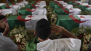 جزائري يلقي التحية أمام رفات المناضلين ال24، 4 تموز/يوليو