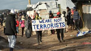 """Un réfugié brandissant une pancarte """"Nous ne sommes pas des terroristes"""" lors du démentèlement de la """"jungle"""" de Calais, en France, en février 2016."""