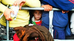 Un enfant attend de pouvoir monter dans un bus, en Autriche, près de la frontière hongroise, le 10 septembre 2015