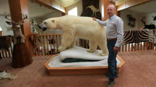 Le chasseur Rod Brandenburg pose aux côtés d'un ours polaire empaillé tué par ses soins dans l'Arctique en 2006.