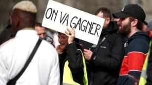 """متظاهرة تحمل لافتة كُتب عليها """"سنفوز"""" في باريس، فرنسا 23 مارس آذار 2019"""