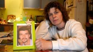 Karine Olivier pose chez elle, Bazouges-La-Pérouse le 22 février 2021, avec la photo de son époux décédé d'un glioblastome à l'âge de 43 ans