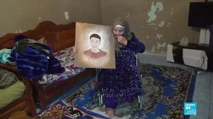 A bereaved mother clings to a portrait of her son who died ten years ago during the Arab Spring uprising.