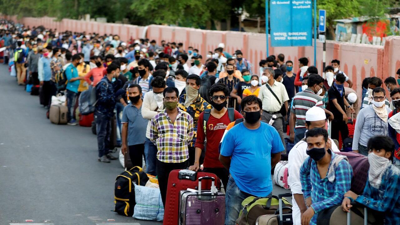 عمال مهاجرون وأسرهم خارج محطة للسكك الحديدية للعودة إلى ولايتهم غرب البنغال. أحمد آباد، الهند في 18 يونيو/حزيران 2020.