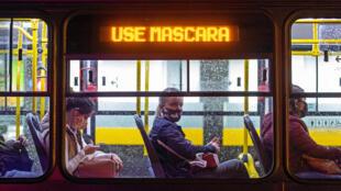 """ركاب يضعون الأقنعة الواقية في حافلة من النقل العام كُتب عليها """"ضعوا كمامة"""" في كوريتيبا في البرازيل في 22 أيار/مايو 2020"""