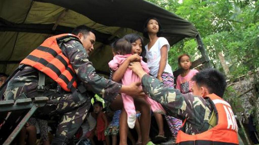 إجلاء أسرة من سورسوغون جنوب مانيلا مع اقتراب الإعصار نول في 8 أيار/مايو 2015