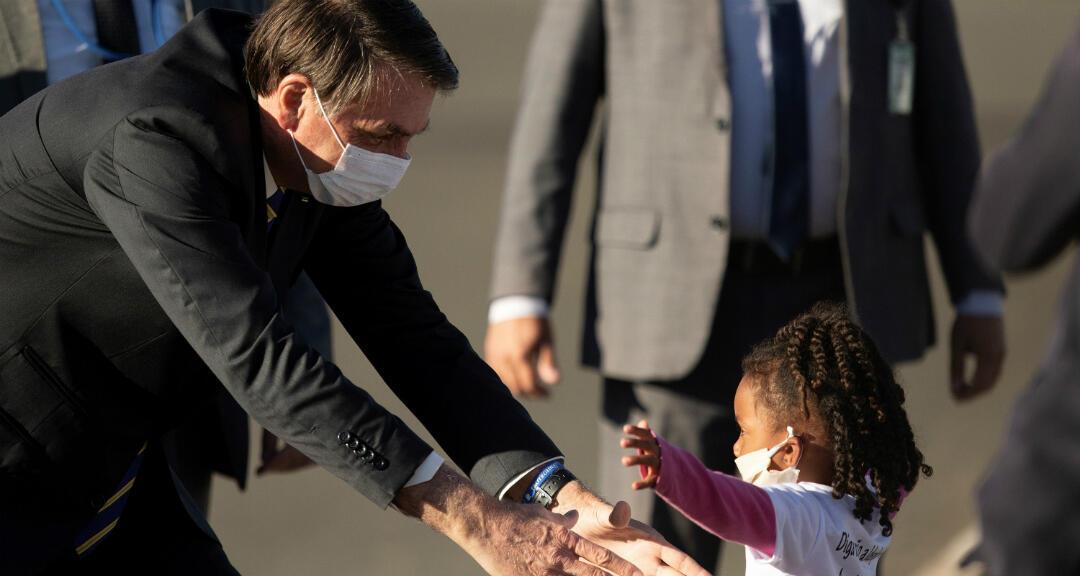 El presidente de Brasil, Jair Bolsonaro, se dispone a alzar a un niña mientras participa en la ceremonia de izada de bandera, frente al Palacio de Alvorada en Brasilia, Brasil el 12 de mayo de 2020.