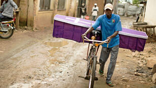Un homme pousse un cerceuil sur son vélo dans les rue de la capitale burundaise Bujumbura en janvier 2016.