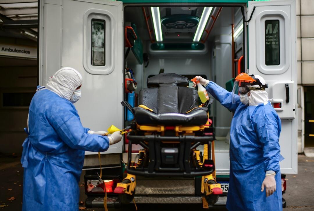 Dos médicos del Sistema de Emergencia Médica (SAME) de Buenos Aires, Argentina, desinfectan una camilla de asistencia el 20 de mayo de 2020.