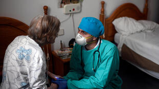 طبيب فنزويلي يمسك بيد مسنة معزولة في أحد دور الرعاية في مدريد في 24 نيسان/أبريل 2020
