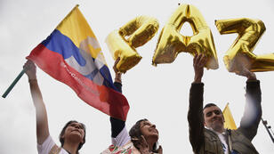"""Des étudiants colombiens participent le 30 septembre 2016 à une manifestation en faveur du """"oui"""" au référendum sur l'accord conclu avec les Farc. Ils brandissent le mot """"paix""""."""