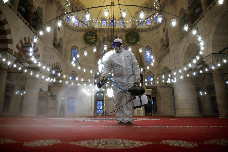 عامل بلدية يرتدي بذلة واقية يقوم بتطهير مسجد كيليك علي باشا بسبب مخاوف من الإصابة بفيروس كورونا في إسطنبول، تركيا، 11 مارس/ آذار 2020.