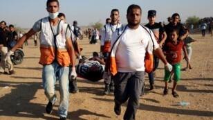 مسعفون ينقلون جريحا فلسطينيا أصيب خلال المواجهات مع الجيش الإسرائيلي شرق خان يونس جنوب قطاع غزة في 24 آب/اغسطس 2018