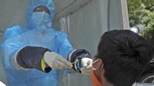 Un trabajador sanitario recoge una muestra de un niño para realizar una prueba gratuita de COVID-19 el 17 de julio de 2020 en Hyderabad, India