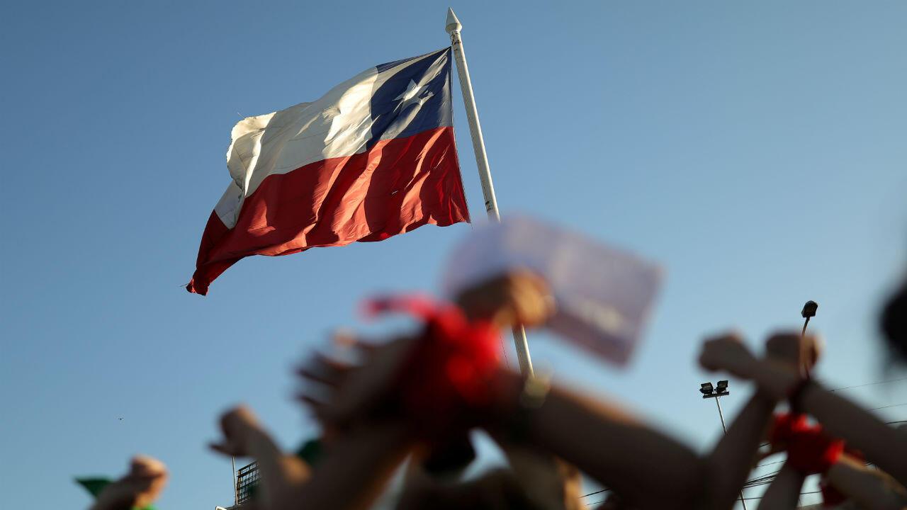 Activistas levantan sus manos atadas cerca de una bandera chilena durante una protesta contra la violencia contra las mujeres y el gobierno de Chile en Santiago, Chile, el 4 de diciembre de 2019.