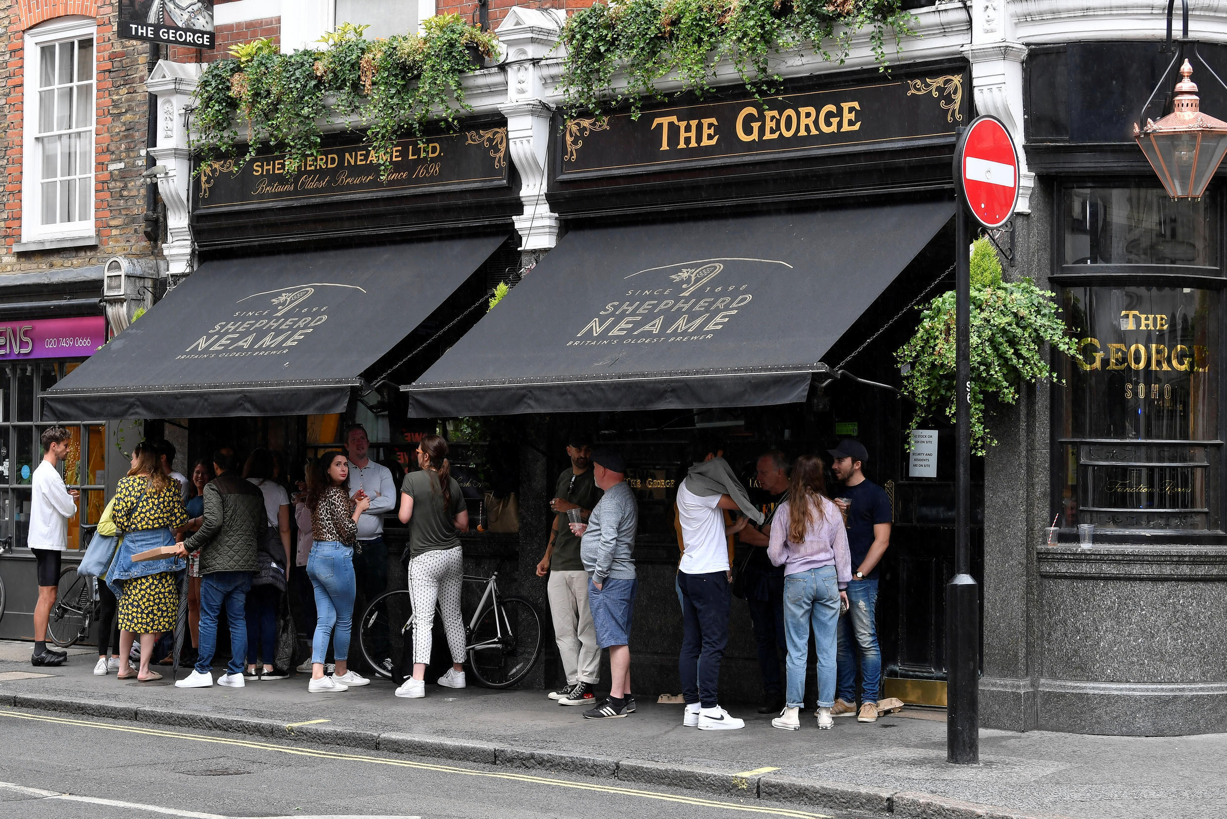 People gather outside a pub amid the spread of the coronavirus disease (COVID-19) in London, UK, June 28, 2020.