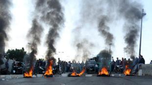 Des manifestants se tiennent près de pneus en flammes bloquant une route à Khaldeh, au Liban, le 13novembre2019.