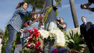 Une femme et sa fille installent un mot sur un lampadaire devenu lieu de recueillement à quelques mètres de la synagogue dans laquelle a eu lieu une fusillade mortelle samedi 27 avril 2019, à Poway, en Californie.