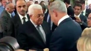 لقطة من تسجيل فيديو يبدو فيه نتانياهو مصافحا عباس خلال تشييع الرئيس الإسرائيلي شيمون بيريز