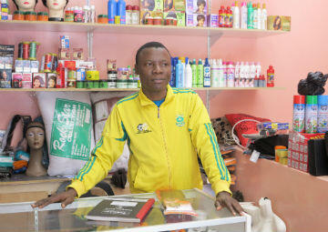 Martial, a 30-year-old from Cameroon, runs a small clothing and accessories shop with his big sister and little brother. He has lived in Sunnyside since 2010.