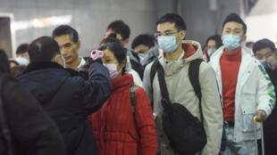 Les passagers d'un train en provenance du Wuhan arrivant à la gare de Hangzhou, le 23 janvier 2020, se font prendre la température.