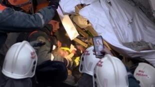 رجال انقاذ ينقلون طفلا نجا من الانفجار في ماغنيتوغورسك