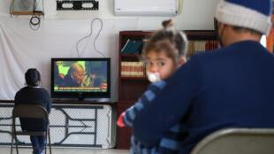 Migrantes centroamericanos miran la toma de posesión de Joe Biden en un refugio en Ciudad Juárez en el norte de México.