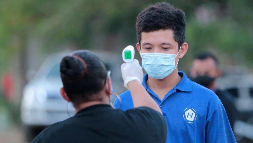 Archivo- A un trabajador de la competencia de fútbol, Liga Primera Nicaragua le toman la temperatura en Managua, el 9 de mayo de 2020-