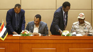 Le général Mohammed Hamdan Daglo, numéro deux du Conseil militaire, et Ahmed al-Rabie, leader de la contestation, signent la déclaration constitutionnelle lors d'une cérémonie à Khartoum, le 4 août 2019.