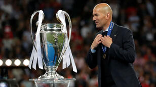 El entrenador del Real Madrid, Zinedine Zidane, al lado del trofeo de la Champions League, en Kiev, Ucrania, el 26 de mayo de 2018.