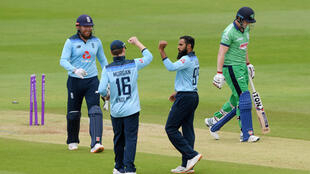 Adil Rashid (2nd R) celebrates with England captain Eoin Morgan after dismissing Ireland's Kevin O'Brien
