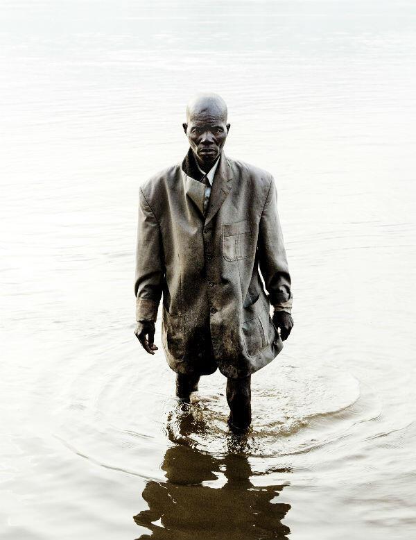Un pêcheur habillé pour la messe dominicale marche sur la rivière Oubangui, tôt le matin.