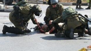 جنود إسرائيليون يحاولون مساعدة جندي طعنه شاب فلسطيني الجمعة 16 تشرين الأول/أكتوبر 2015