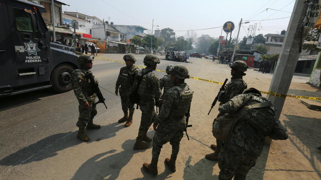 Oficiales de policía y personal militar trabajan en una escena del crimen cerca de un auto quemado en Acapulco, México, el 7 de mayo de 2019.