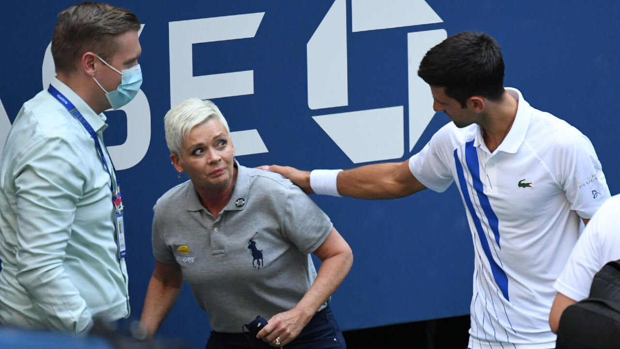 Novak Djokovic and a tournament official tend to a linesperson who was struck with a ball by Djokovic on September 6, 2020, day seven of the 2020 US Open, in Flushing Meadows, New York, USA.
