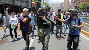 Un miembro de la Guardia Nacional Bolivariana levanta un puño luego de unirse a manifestantes antigubernamentales en una marcha a favor del líder de la oposición, Juan Guaido. en Caracas, Venezuela, 30 de abril de 2019.