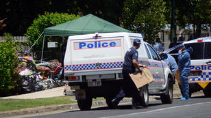 Police carry evidence bags at the scene where eight children were found dead at a home in the northern Australian city of Cairns.
